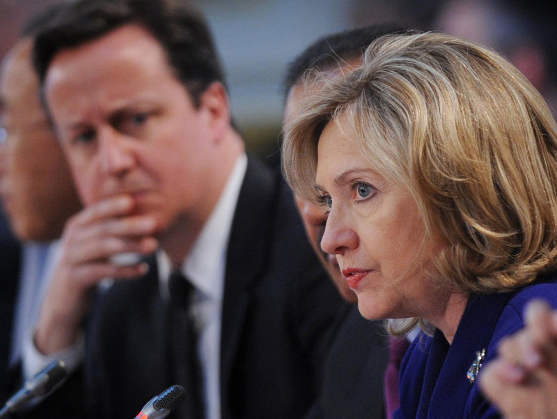 British Prime Minister David Cameron listens as U.S. Secretary of State Hillary Rodham Clinton speaks Tuesday at a conference on Libya in London. Forty world leaders attended the talks, seeking to ratchet up the pressure on Col. Moammar Gadhafi to step down. Gadhafi has lost the legitimacy to lead, so we believe he must go, Clinton said.