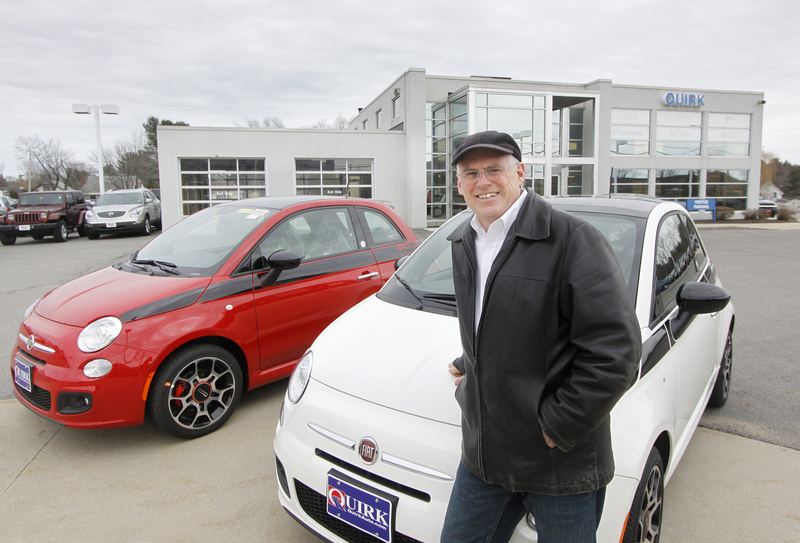 Jack Quirk shows off two new Fiat 500 cars at his dealership in Portland. In the background is the building being renovated to be the new Fiat studio.