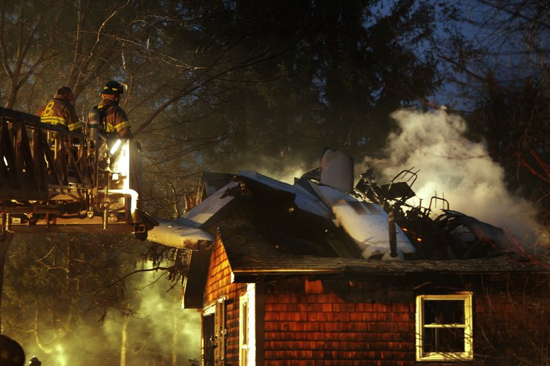 Biddeford firefighters move a ladder closer to an airplane that crashed into a house on Granite Street Extension in Biddeford tonight.