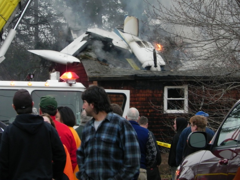 A crowd gathers at the Biddeford home where an airplane crashed about 6 p.m. today.