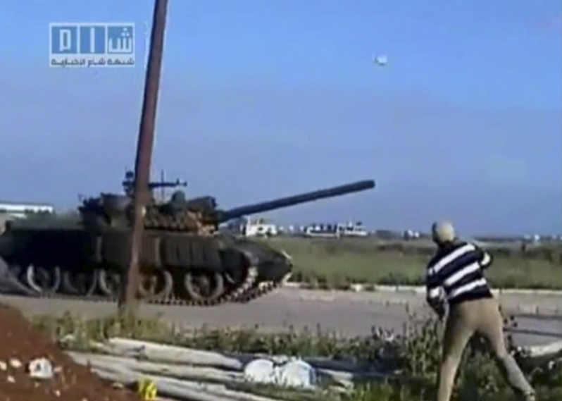 An image taken from amateur video shows a man throwing an object at a tank Sunday in Daraa, Syria. Troops and tanks stormed the town early Monday and opened fire, reportedly killing dozens of protesters.