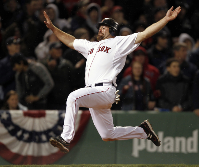 Boston Red Sox's Kevin Youkilis goes flying into home to score on a double by David Ortiz during the eighth inning of Boston's 4-0 win over the New York Yankees Sunday at Fenway.