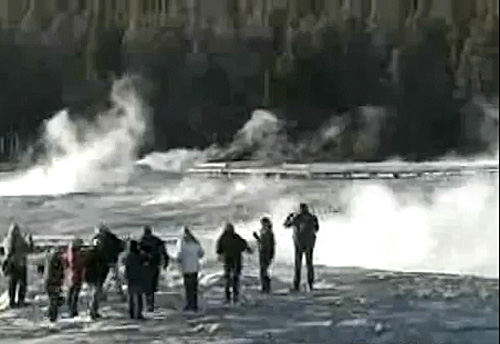 A group of tourists stand dangerously close to the iconic Old Faithful geyser in Yellowstone National Park in Wyoming on Wednesday, April 27, 2011, in this still made from National Park Service video.