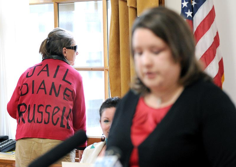 A lone protester who refused to give her name stands in the background as Rep. Diane Russell holds a press conference on her bill to legalize and tax marijuana.