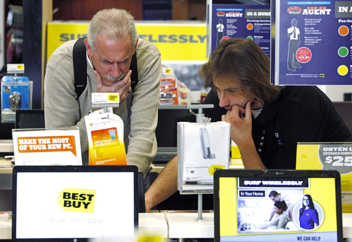 A customer shopping for a laptop computer is assisted by a Best Buy sales associate in Glendale, Calif., Wednesday.