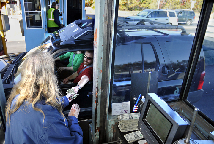 A driver receives his change from a toll collector at the York Toll plaza. The turnpike authority employs 250 full-time and part-time toll collectors.