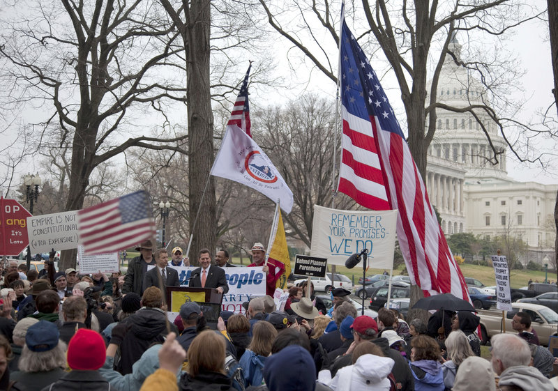"""In a steady drizzle, about 500 people staged a tea party """"Continuing Revolution Rally"""" Thursday on Capitol Hill in Washington, chanting, """"We want less."""" But no major Republican congressional leaders showed up."""