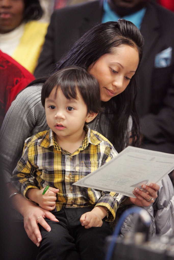Alice Ker, originally from France, examines her naturalization certificate with her son, Kash, 3.