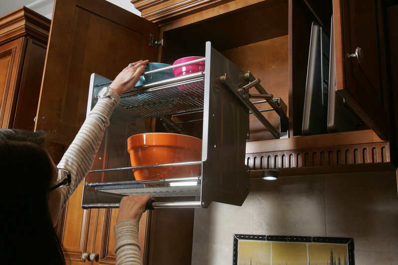 A convenient pull-down rack maximizes space usage in an upper kitchen cabinet. Vertical racks (at right) hold baking and cookie sheets.
