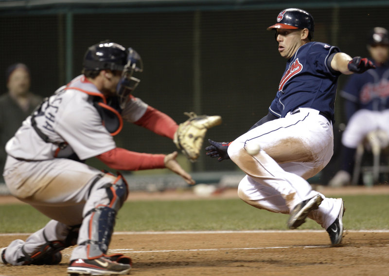 Asdrubal Cabrera of the Cleveland Indians slides safely to the plate, scoring on a sacrifice fly as Boston catcher Jarrod Saltalamacchia waits for the throw Tuesday.