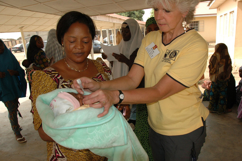 Ann Lee Hussey of South Berwick administers polio vaccine to an infant outside Kaduna Hospital in Nigeria as part of a Rotary International program.