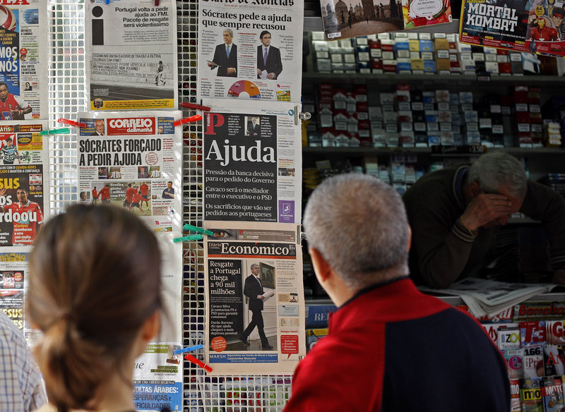 People in Lisbon, Portugal, look at newspapers' front pages Thursday. Prime Minister Jose Socrates said late Wednesday that Portugal will ask for a bailout to relieve its crushing debt, joining Greece and Ireland in seeking outside help amid a bruising financial crisis.