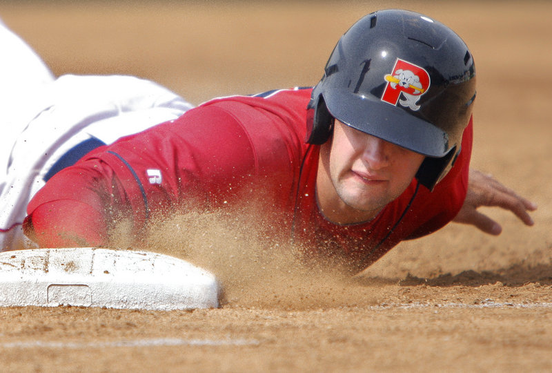 Portland's Alex Hassan dives back to first base in the third inning of the Sea Dogs against the Phillies on Sunday afternoon at Hadlock Field. Portland beat Reading 2-0 to close its season-opening series with 2 wins and 2 losses.
