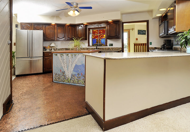 Mosaic artist Amanda Edwards used pennies to create a one-of-a-kind floor for the kitchen of her Falmouth home. The space also includes a mosaic of cut stained glass over her kitchen counter, a colored tile mosaic on the island, and a backsplash covered with pebbles, sea glass and shells her children have collected.