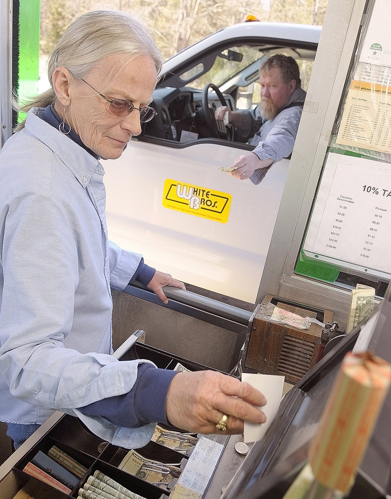 Toll collector Sheila Baucom takes tolls from southbound motorists Thursday at the toll plaza on the Maine Turnpike in West Gardiner.