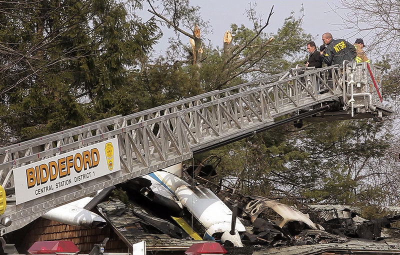 On Monday, an investigator with the National Transportation Safety Board surveys the wreckage of a plane that crashed into a Biddeford house Sunday night, killing the pilot.