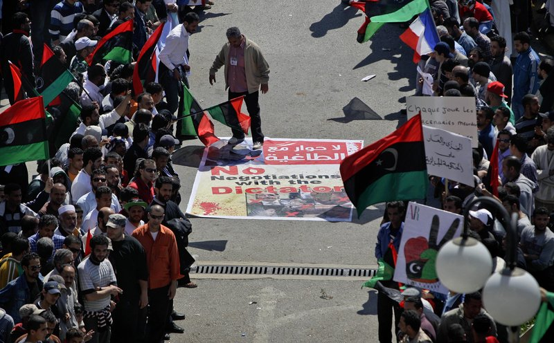 "An angry but peaceful crowd lines the route to the Tibesty Hotel where an African Union delegation met with opposition leaders in Benghazi, Libya on Monday. Of Moammar Gadhafi, protester Jalil Tabouri said: ""He is the biggest lier in the history of Libya."""