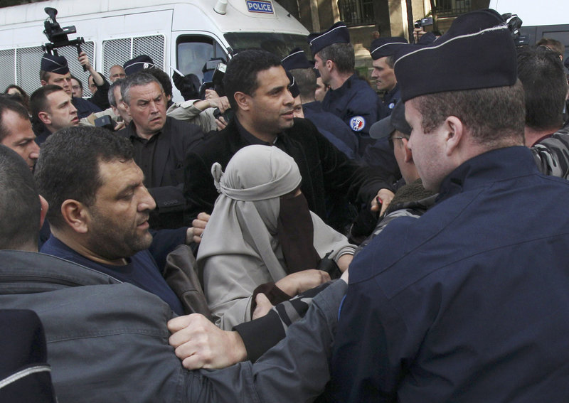 An unidentified veiled woman, flanked by a friend, center right, is taken away by police officers in Paris on Monday. Within hours of a new ban on Islamic face veils Monday, two veiled women were detained for taking part in an unauthorized protest.