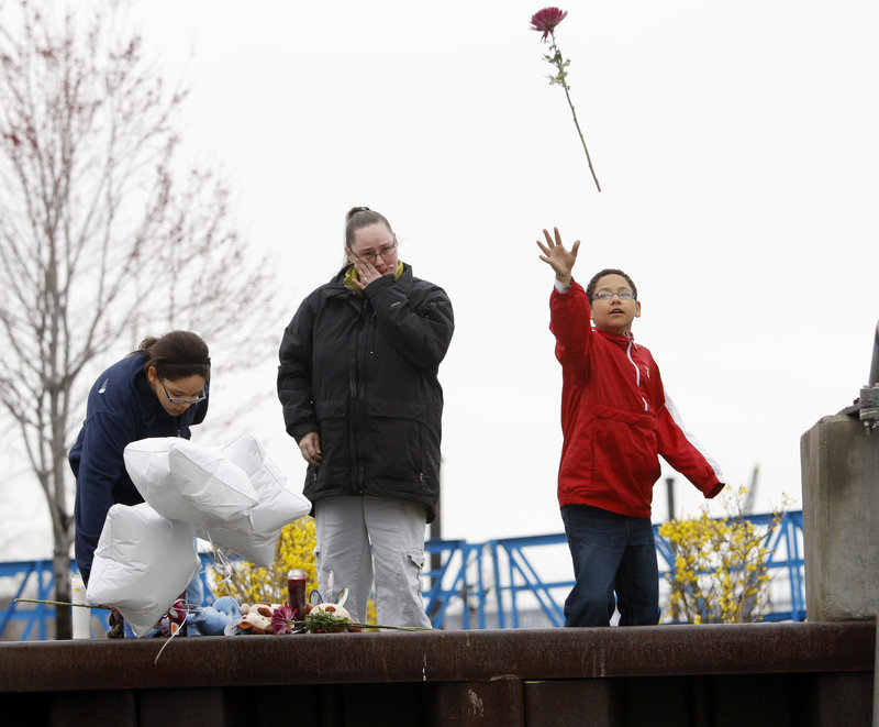 Demetrius Galloway, right, throws a flower into the Hudson River on Wednesday at a boat launch where a woman drove her minivan and four of her children into the water.
