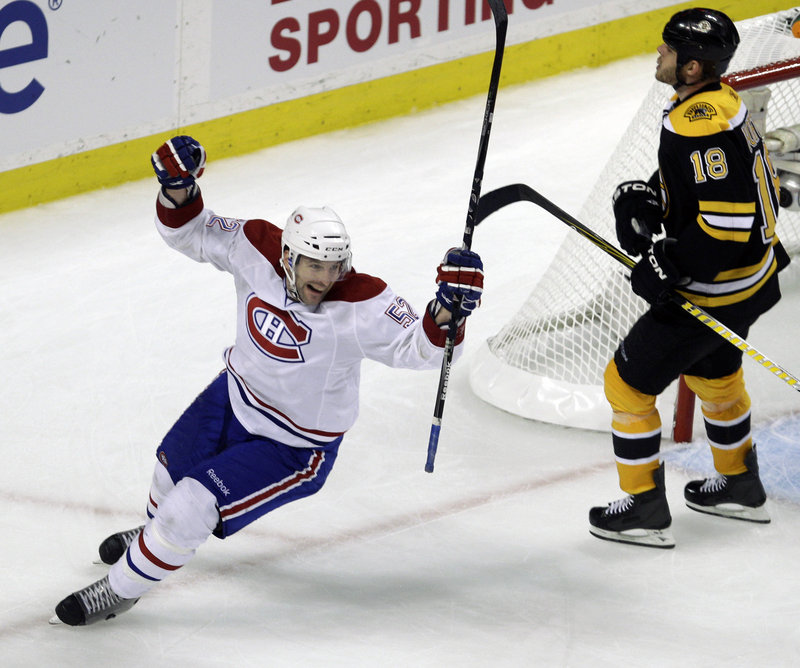 Mathieu Darche skates past Boston's Nathan Horton while celebrating the second goal by Brian Gionta. The Canadiens took a 1-0 lead in the best-of-seven series.