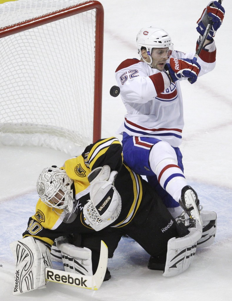 Bruins goalie Tim Thomas knocks away the puck as Canadiens left wing Mathieu Darche falls onto him in Montreal's 2-0 playoff win Thursday night at Boston.