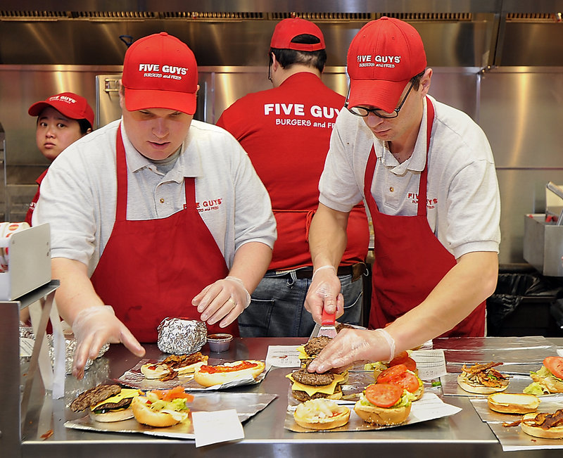 Manager Josh Montalto, left, and burger griller Milen Nikolov fill lunch orders at Five Guys.