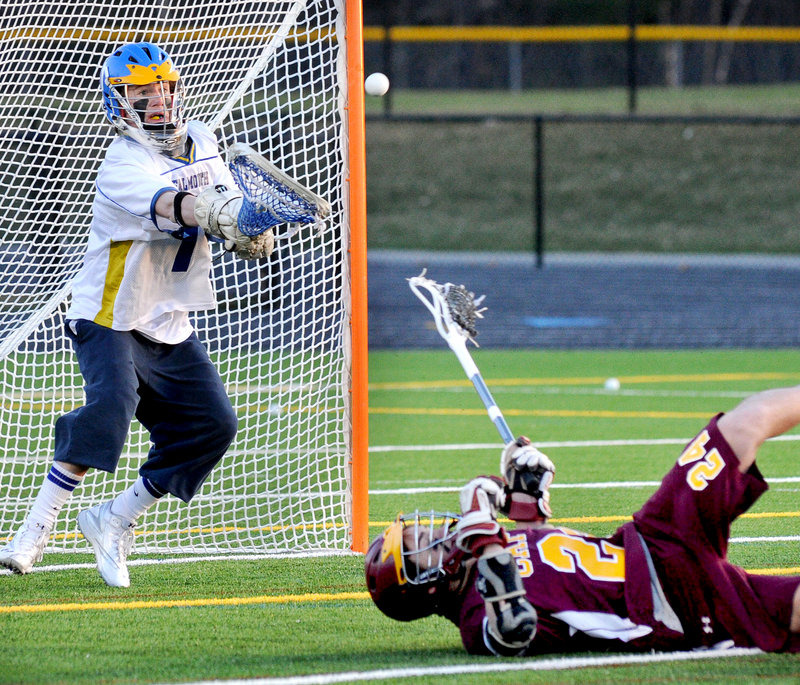 Falmouth goalie Cam Bell focuses on making a save against Wes Richards of Cape Elizabeth, who fell after taking a shot during their schoolboy lacrosse game Friday at Falmouth High. Falmouth won, 12-4.