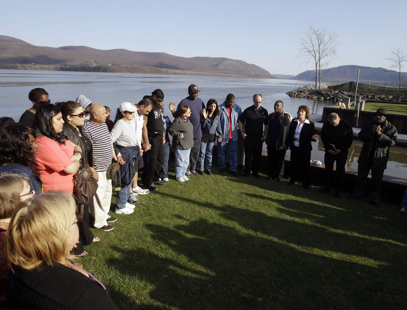 People attend a vigil on Thursday at the boat ramp In Newburgh, N.Y., where Lashanda Armstrong drove her minivan into the Hudson River on Tuesday night, killing herself and three of her children.