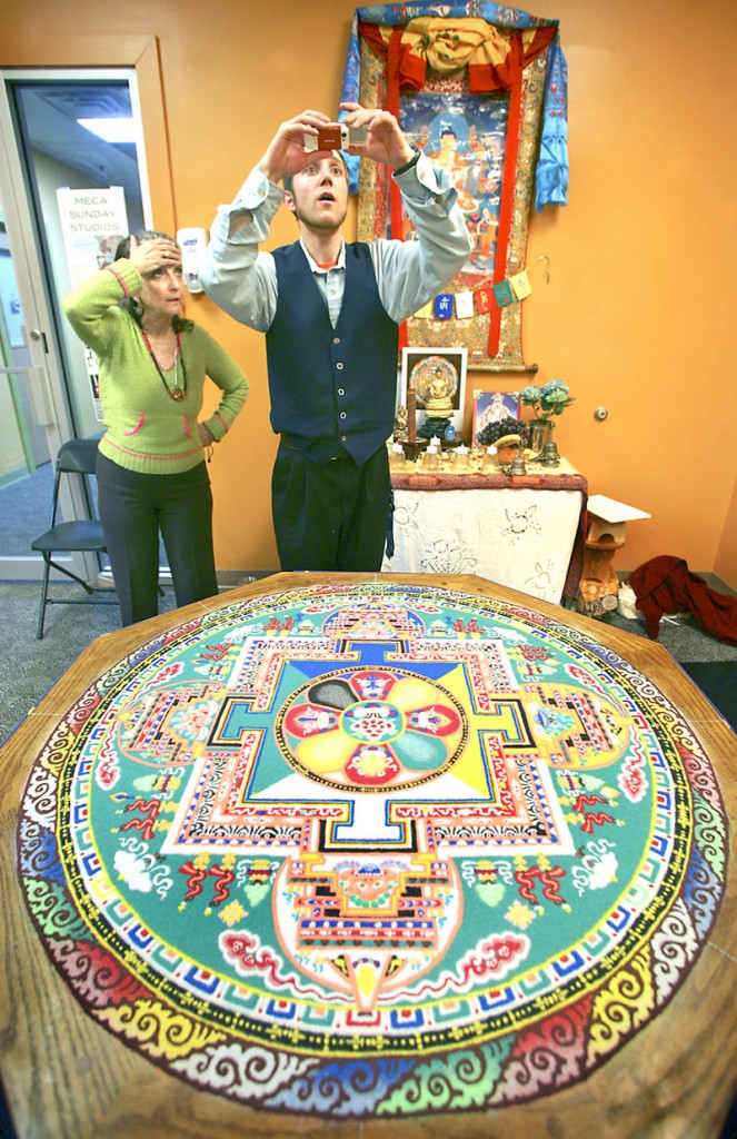 Gerald Pound of Gorham takes a photograph as Louisa-Lora Somlyo of Portland looks on before the deconstruction ceremony of a sand mandala on Sunday.