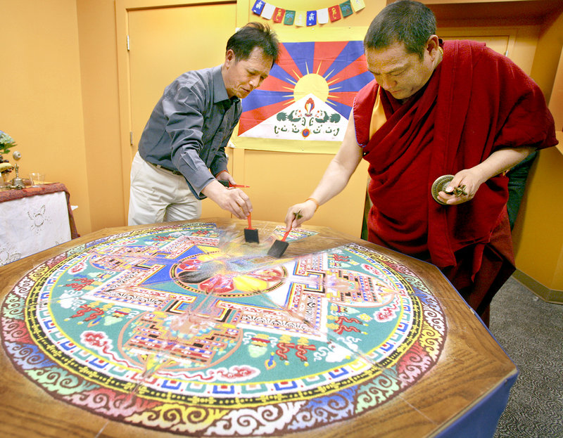 Former Tibetan Buddhist monk Sonam Dhargye, left, and Tibetan Buddhist monk Geshe Gendun Gyatso sweep up sand on Sunday during the deconstruction ceremony of a sand mandala that they created. The mandala was created last week by Tibetan Buddhist monks at the Maine College of Art in Portland.