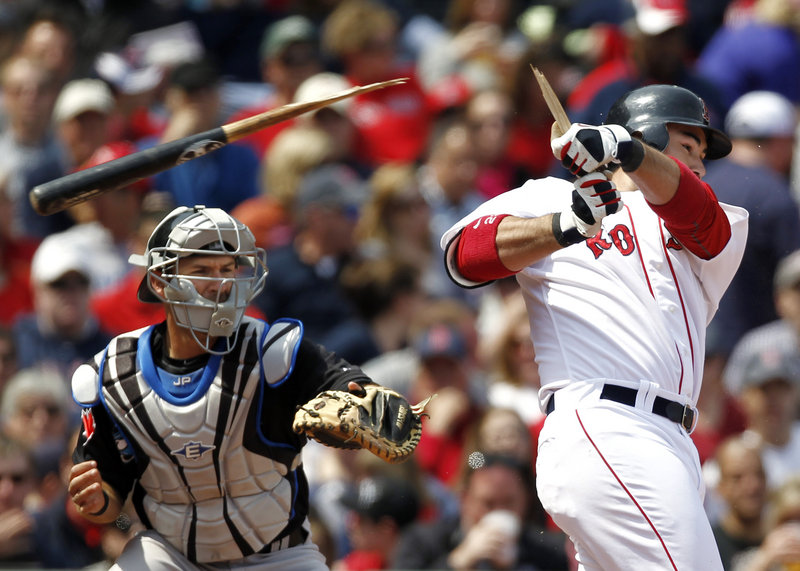 Boston's Adrian Gonzalez shatters his bat on a ground out as Toronto catcher J.P. Arencibia looks on during the sixth inning of Boston's 9-1 win Monday at Fenway Park. The Sox rapped out 13 hits and three home runs against the Blue Jays.