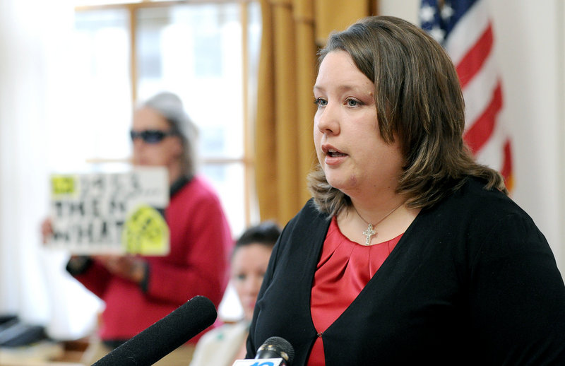 Rep. Diane Russell holds a press conference at Portland City Hall Wednesday, where she explained her bill to legalize marijuana and tax its sales, raising an estimated $8.5 million each year, she said. A lone protester in the background holds a sign opposing her bill.