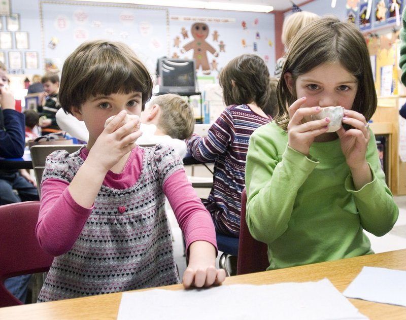 """Eleanor Bidwell, 6, and Sophie Galin, 7, sip tea in a lesson based on """"Three Cups of Tea"""" at Hall Elementary School in Portland in 2009. Hall students made their own cups and raised $481.06 for schools in Afghanistan and Pakistan."""