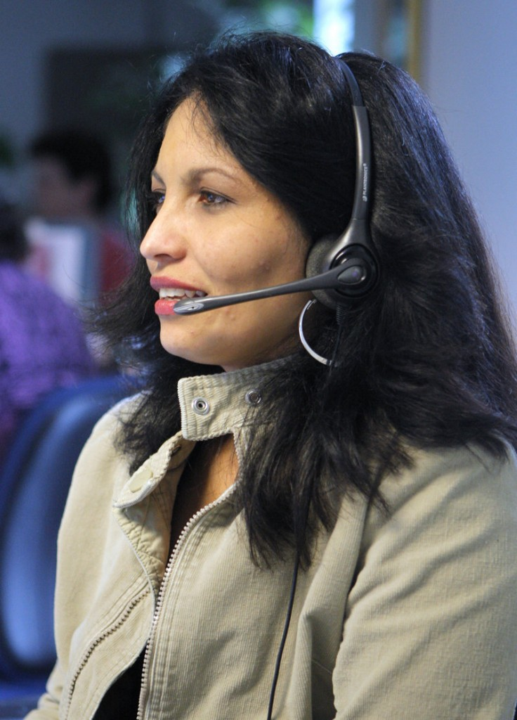 Justina Velez talks with a customer while working in the call center at Wright Express in South Portland. Velez is a bilingual customer service representative, working with customers who speak English or Spanish.