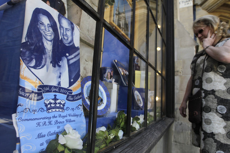 A passer-by checks out a display of souvenirs of Prince William and Kate Middleton in a Westminster Abbey shop window in London on Friday. The couple are to marry April 29 at Westminster Abbey.