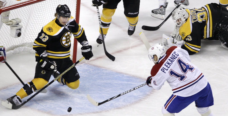 Boston forward Michael Ryder, left, drops to his knees before lifting his glove to slap away a shot by Montreal's Tomas Plekanec in the first period Saturday night. Ryder's save preserved a 0-0 tie. Boston went on to win 2-1 in OT.