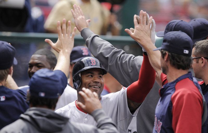 Carl Crawford is greeted by his teammates after hitting his first home run as a member of the Red Sox – a two-run blast in the sixth inning Sunday against the Angels.