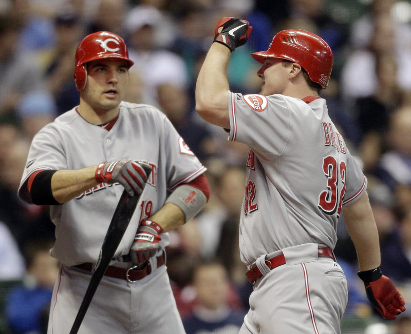 Jay Bruce, right, is congratulated by teammate Joey Votto after Bruce hit a two-run home run during the third inning in Milwaukee. The Reds scored six runs in the inning.