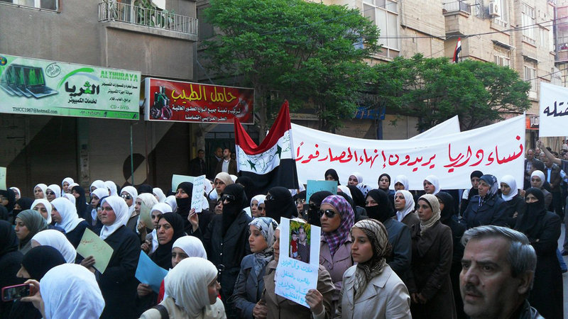 "Syrian women carry a banner in Arabic that reads: ""The women of Daraa want an end to the siege,"" as they protest in Daraa, southwest of Damascus, on Monday, in this image made on a mobile phone and acquired by The Associated Press."