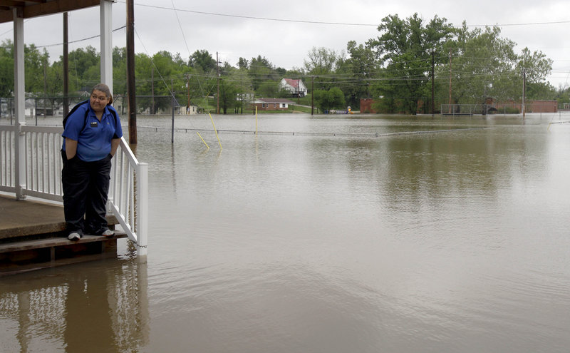Erica Cross stands on a friend's porch surrounded by floodwater Tuesday in Poplar Bluff, Mo, where 6 inches of rain fell Monday alone, bringing the four-day total to 15 inches.