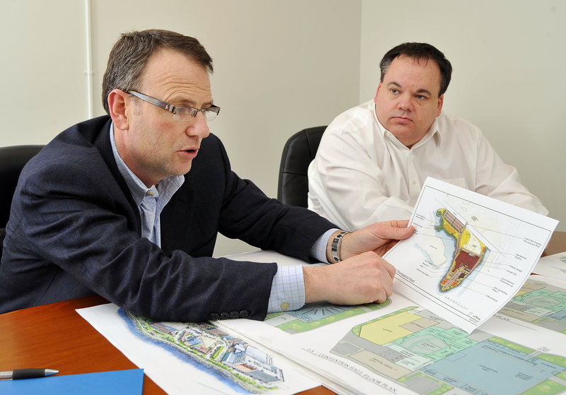 Bill Ryan Jr., left, and Jon Jennings, two co-owners of the Red Claws, examine details of a proposed arena.