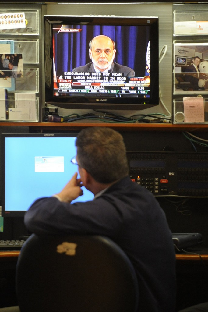 Sean Spain of Goldman Sachs watches Ben Bernanke on television Wednesday from the New York Stock Exchange. It was the first time in the Fed's 98-year history that a chairman has begun holding regular sessions with reporters.