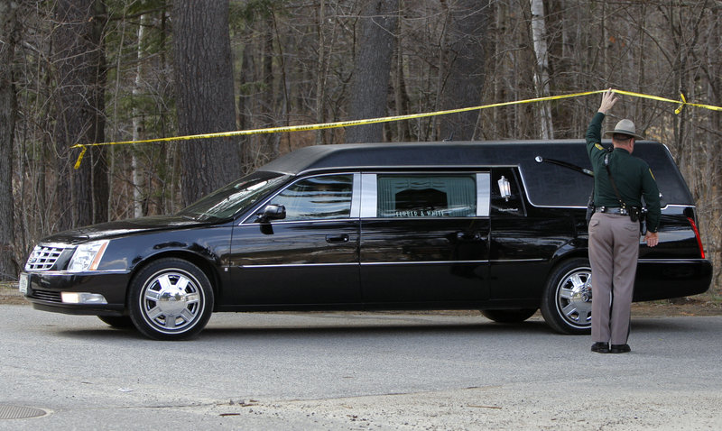A New Hampshire State Police trooper holds up police tape so a hearse can pass underneath in North Conway, N.H., on Wednesday.