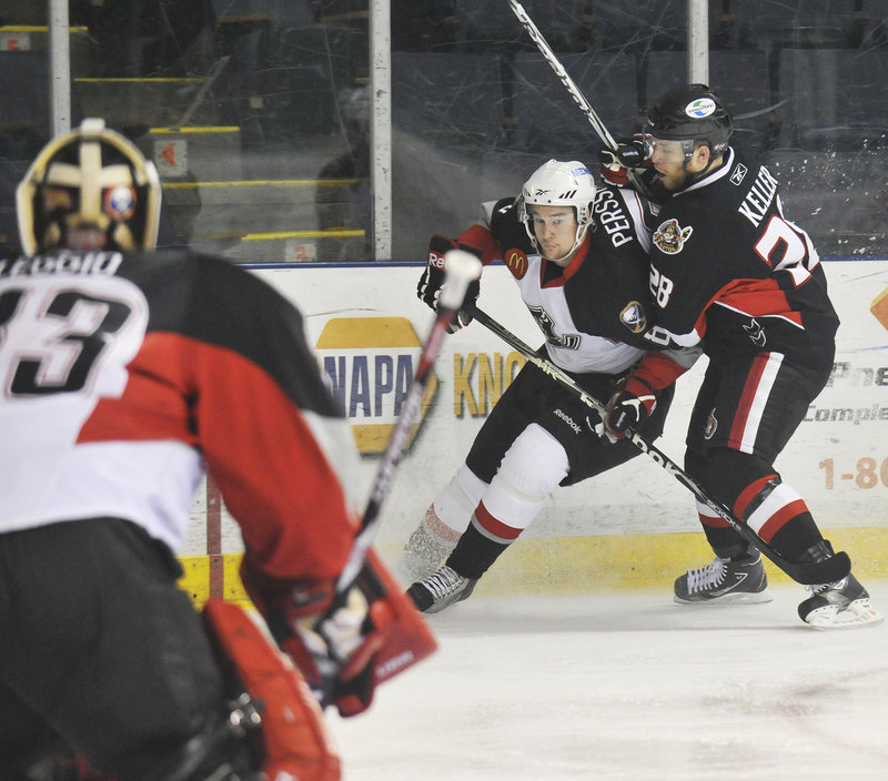 Ryan Keller of Binghamton, right, tries to ride Portland's Dennis Persson off the puck in front of goalie David Leggio during Game 1 of their division series Wednesday night at the Cumberland County Civic Center. The Senators won, 3-2.