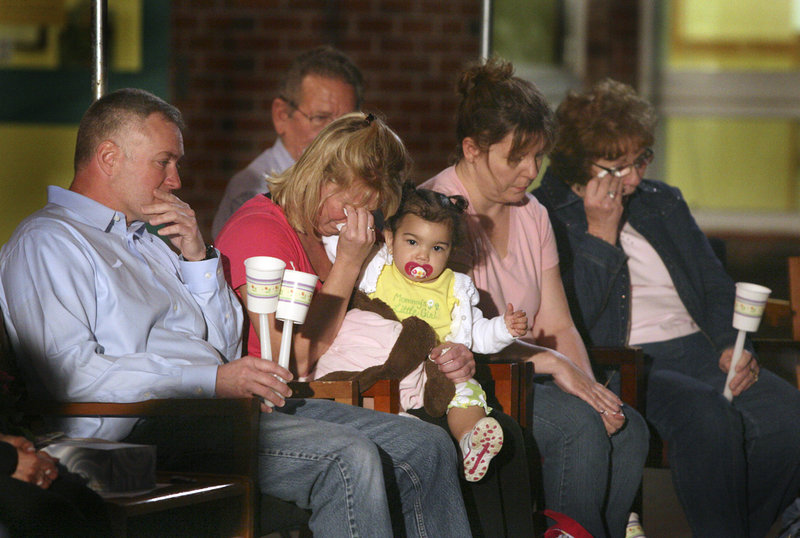 """Krista Dittmeyer's mother, LaNelle Shackley, holds Krista's 14-month-old daughter, Aliyah, during the candlelight vigil for the Portland woman at the Stevens Brook Elementary School in Bridgton on Thursday night. Kayla Dittmeyer of Denver spoke in tribute to her sister, saying, """"I hope you see how many people care about you."""""""