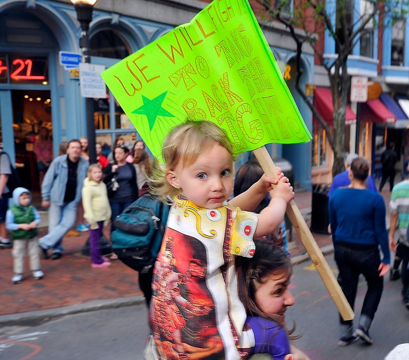 Two-year-old Sadie Catalogna waves a sign from her perch atop her mom, marcher Kristina Catalogna of Portland.
