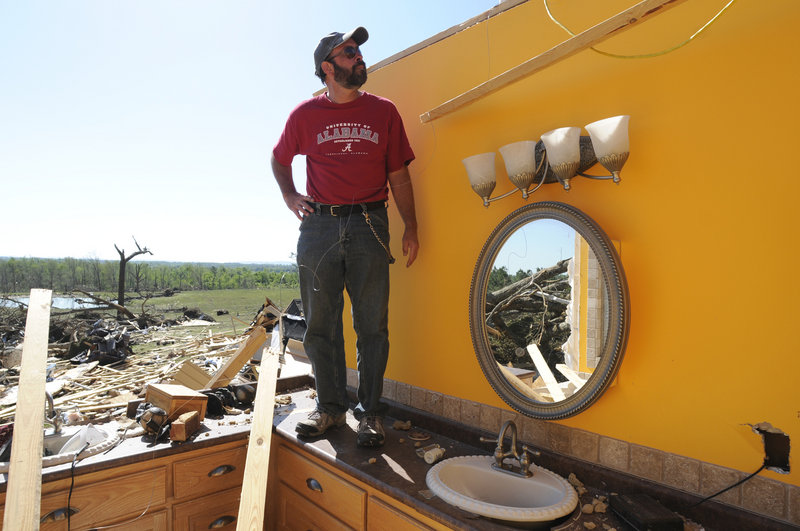 Allen Hamilton stands on the bathroom counter in the wreckage of his home Friday in Rainsville, Ala. Hamilton and his family survived a tornado Wednesday by taking refuge in a closet next to the bathroom.