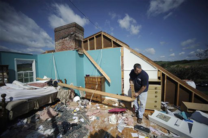 Shane Gilland sorts through the wreckage of his father's home in Bethel, Va., today. Gilland's father and stepmother Gail survived when a tornado hit their house early Thursday.