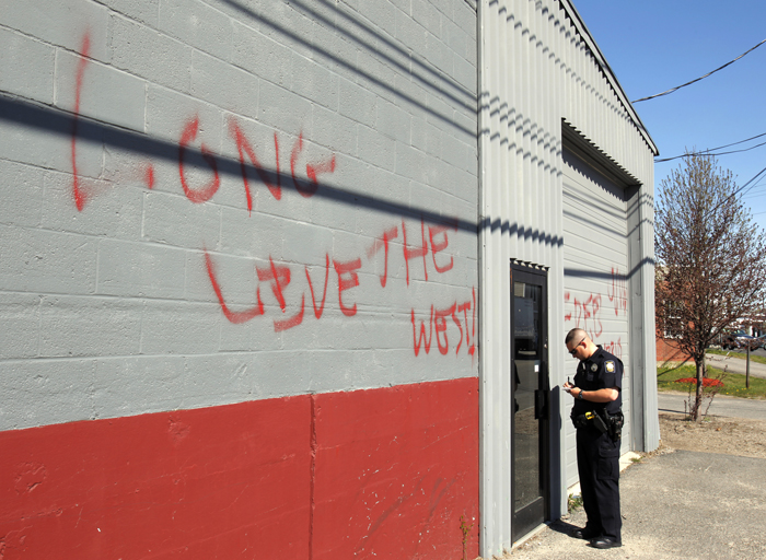 "Officer Gavin Hillard writes down contact information at a mosque on Anderson Street in Portland today where someone spray painted graffiti on the wall in the wake of Osama bin Laden's death. The writing says ""Osama today Islam tomorow (sic),"" and ""Long live the West."""