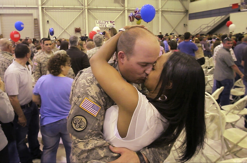 Sgt. Justin Titcomb of Wells and his wife, Joana, embrace Tuesday in Manchester, N.H. Titcomb, a Wells policeofficer, spent a year serving in Baghdad with the 94th Military Police Company.